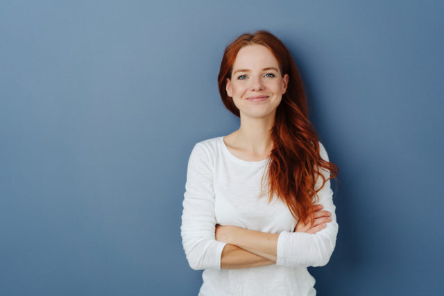Pleased young redhead woman with a beaming smile