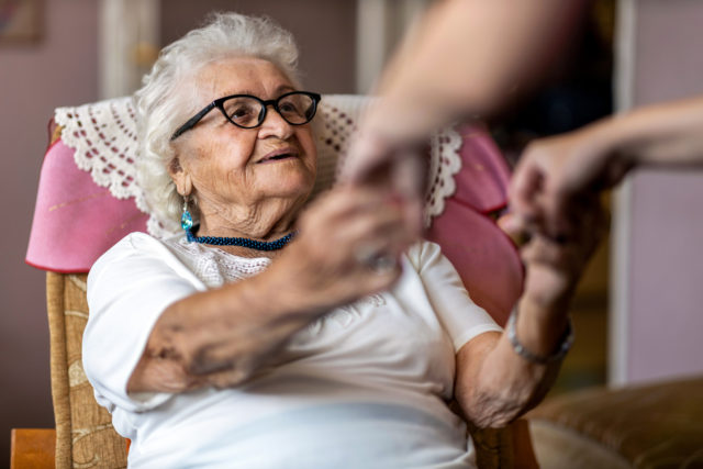 Female home carer supporting old woman to stand up from the armchair at care home