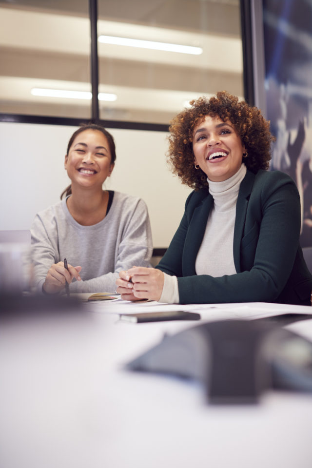 Businesswomen Collaborating In Creative Meeting Around Table In Modern Office